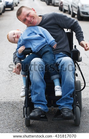 Disabled man with little son on wheelchair - stock photo