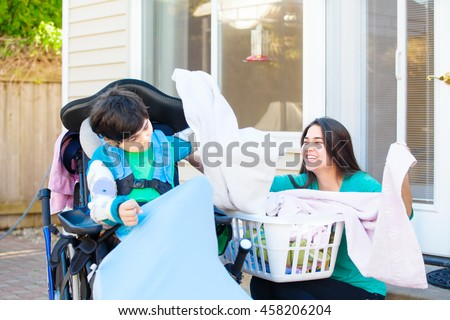 Disabled nine year old boy in wheelchair helping teen sister fold laundry outside on patio - stock photo