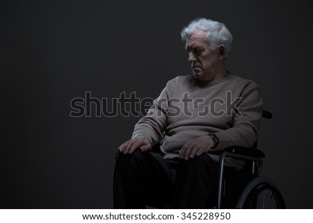 Disabled old man sitting on a wheelchair in empty room - stock photo