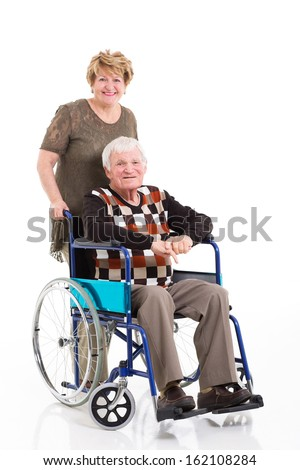 disabled old man sitting on wheelchair with caring wife on white background - stock photo