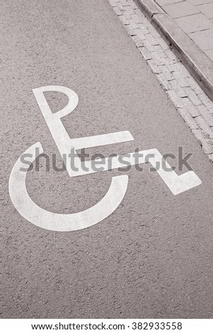 Disabled Parking Sign on Street Surface in Black and White Sepia Tone