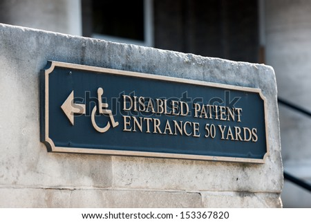 Disabled patient entrance tablet sign on a public stone wall in a capital city. - stock photo
