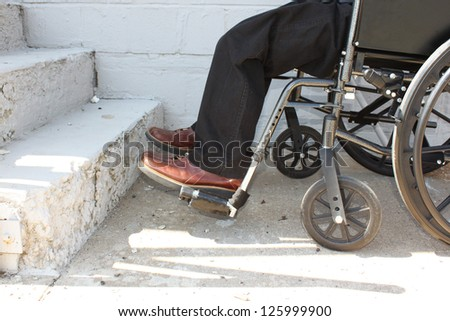 Disabled person in front of the stairs - stock photo
