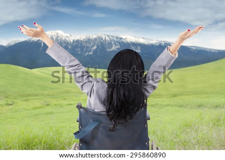 Disabled person raise hands on the meadow while sitting on wheelchair and enjoy mountain fresh air - stock photo