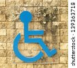 disabled person sign on brick wall - stock photo