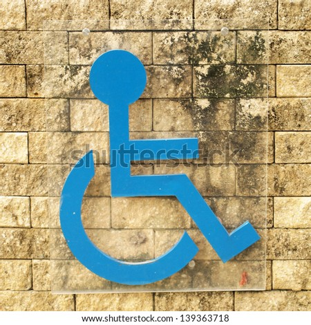 disabled person sign on brick wall