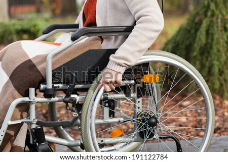 Disabled person sitting on wheelchair in park - stock photo