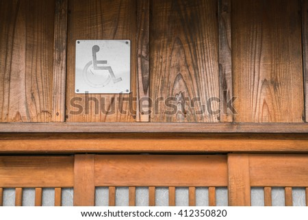 Disabled person toilet sign on old wood wall - stock photo