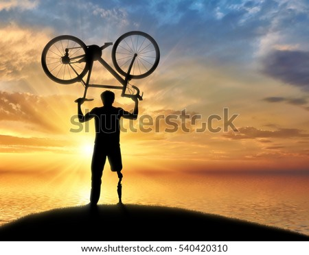 Disabled person with prosthetic leg standing on hill and holding bicycle over his head sea. Concept disabled and sport