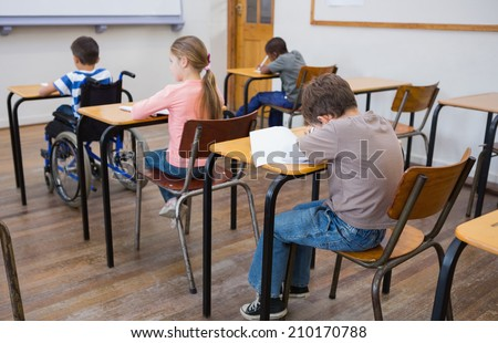 Disabled pupil writing at desk in classroom at the elementary school - stock photo