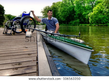 Disabled rower before beginning his training with his wheelchair on boardwalk - stock photo