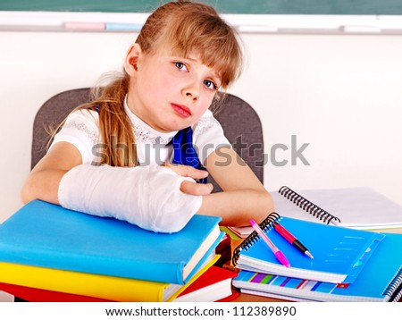 Disabled sad child with broken arm in classroom. - stock photo