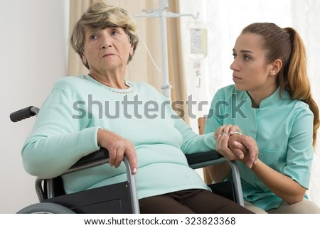 Disabled sad woman living in care home - stock photo