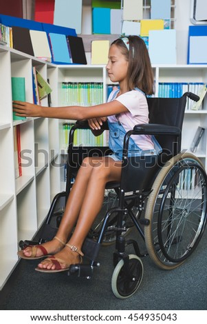 Disabled school girl selecting a book from bookshelf in library at school