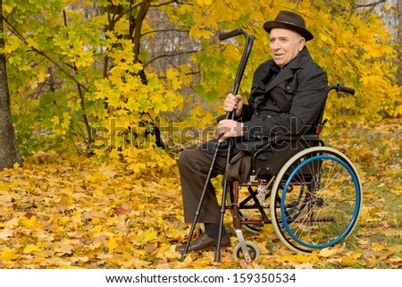 Disabled senior man in a wheelchair sitting in his overcoat and hat in a colourful autumn woodland holding his crutches in his hand, with copyspace - stock photo