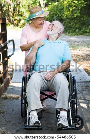 Disabled senior man in wheelchair with his loving wife taking care of him. - stock photo