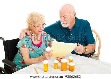 Disabled senior woman and her husband go over their medical and prescription drug bills.  Isolated on white. - stock photo
