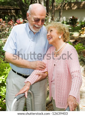 Disabled senior woman looks adoringly at her husband as he helps her walk. - stock photo