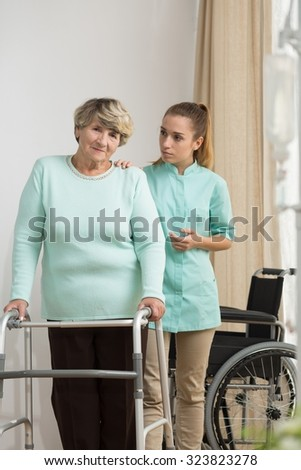 Disabled senior woman standing with walking frame - stock photo