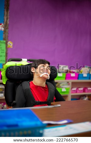 Disabled seven year old boy sitting at desk in classroom - stock photo