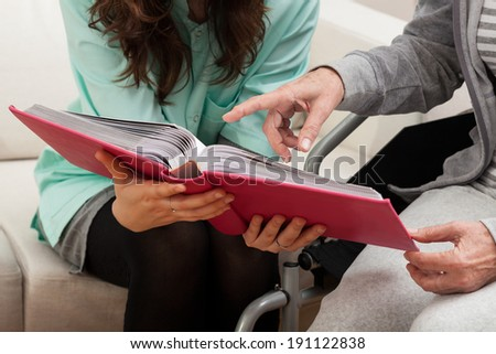 Disabled with nurse viewing family photo album - stock photo