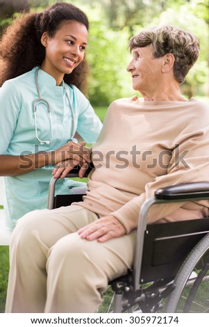 Disabled woman and caring doctor in the garden - stock photo