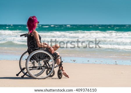 Disabled woman in the wheelchair at the beach enjoying the view - stock photo