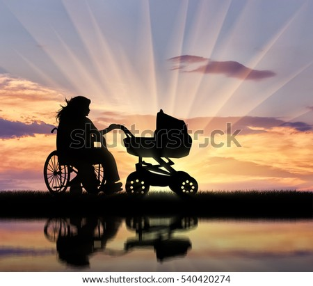 Disabled woman in wheelchair holding stroller sunset and reflection in water. Concept disabled and family