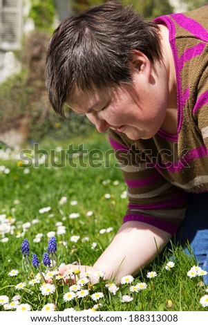 disabled woman is sitting on a green meadow - stock photo