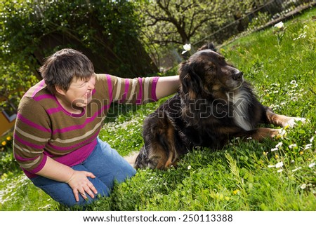 disabled woman on a lawn is stroking a dog - stock photo