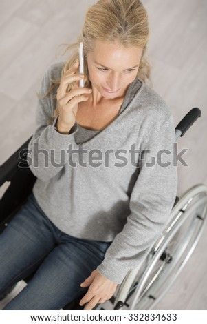disabled woman on wheelchair using a mobil phone
