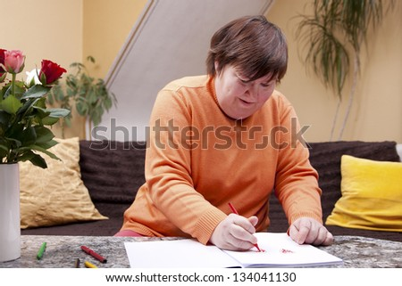 Disabled woman painted with colored pencils in a book - stock photo