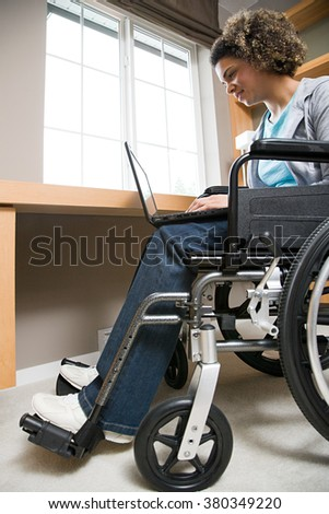 Disabled woman using a laptop computer - stock photo