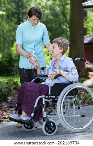 Disabled woman with glass of water in a garden - stock photo