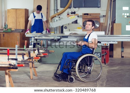 disabled worker in wheelchair in a carpenter's workshop with his colleague - stock photo