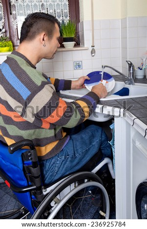 Disabled young man in wheelchair in the kitchen  - stock photo