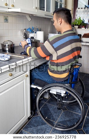 Disabled young man in wheelchair is cooking a meal in the kitchen  - stock photo