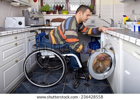 Disabled young man in wheelchair washing clothes - stock photo