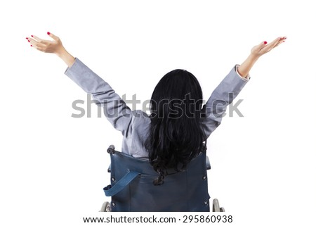Disabled young woman sitting on a wheelchair and raise hands in the studio, isolated on white - stock photo