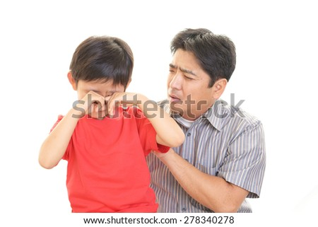 Disappointed Asian child with father - stock photo