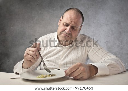 Disappointed fat man eating vegetables