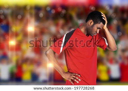 Disappointed football fan looking down against blurry football pitch with crowd - stock photo