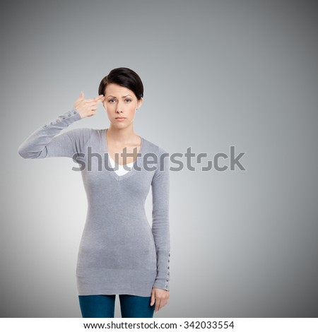 Disappointed girl shows hand gun gesture, isolated on grey - stock photo
