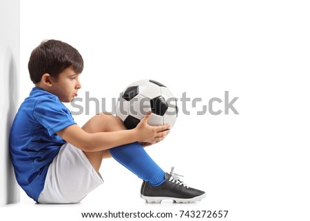 Disappointed little footballer leaning against a wall isolated on white background