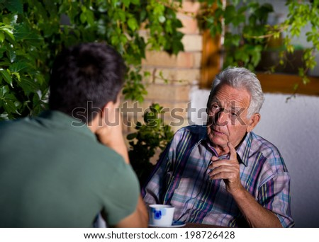 Disappointed old man pointing forefinger in young man - stock photo