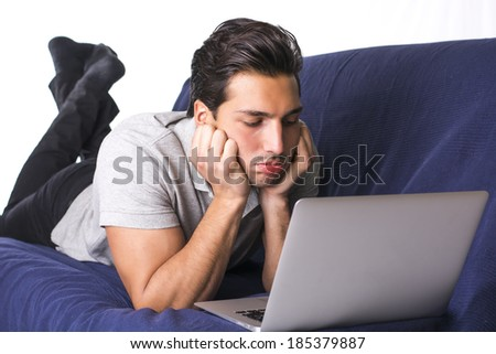 Disappointed or bored young man staring at laptop PC while laying on blue couch
