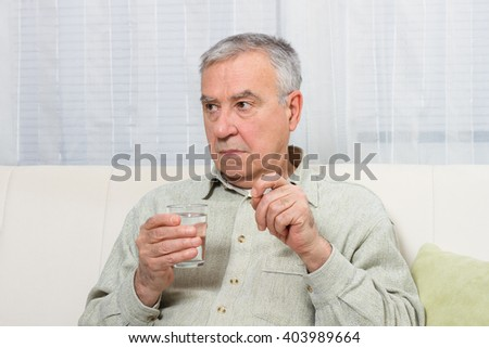 Disappointed senior man is sitting on the sofa and taking pills.Disappointed senior man taking pills - stock photo