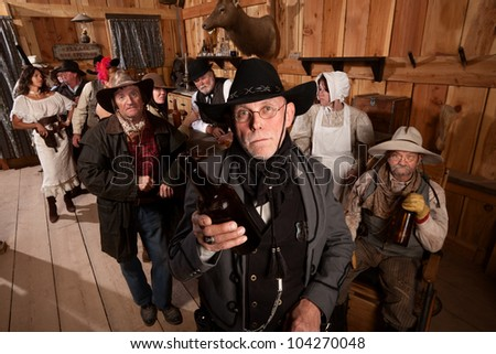Disappointed sheriff holds empty bottle in old west tavern - stock photo