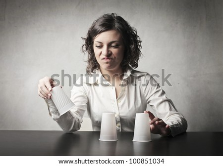Disappointed woman losing at a conjuring trick - stock photo