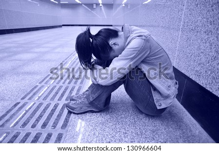disappointed woman sit on subway station - stock photo
